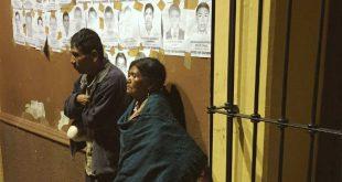 [ARCHIVO] Dos personas esperan junto a fotos de personas desaparecidas en México.