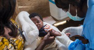Una enfermera se prepara para vacunar a una niño contra el sarampión en la RD Congo.