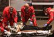 Un hombre con una máscara yace inconsciente en el suelo cerca de una para de autobús, el 22 de marzo en Roma, y es trasladado por las autoridades sanitarias