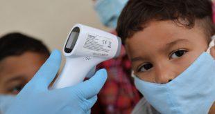Un médico toma la temperatura a una familia de retornados en un refugio temporal en Venezuela. Kariani Rivero de Maroto, de 27 años y sus hijos, Diego y Matías, de 7 y 3 años, regresaron de Colombia después de que ella perdiera su trabajo en una peluquería.